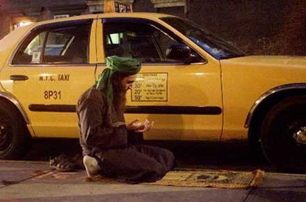 Taxi driver praying (Namaaz) in the parking area.